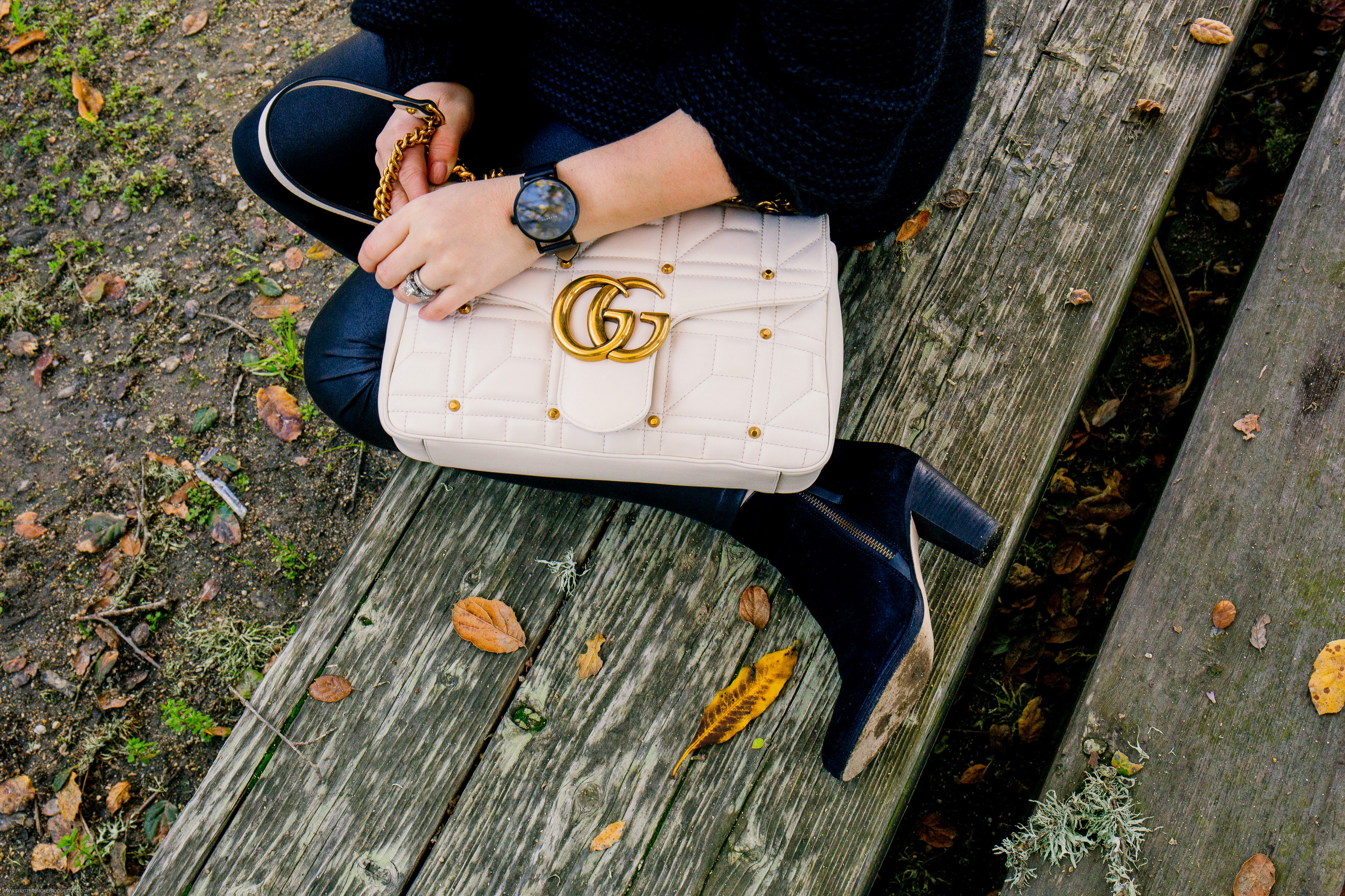 black leather spanx // free people sweater // medium gucci marmont   Designer Handbags by popular Monterey fashion blog, Haute Beauty Guide: image of a woman sitting on a wooden bench and holding a cream leather Gucci handbag.
