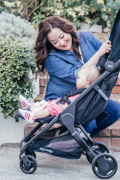Useful Baby Gifts That New Moms Will Actually Use by popular California lifestyle blog, Haute Beauty Guide: image of a woman with her baby sitting in an Ergobaby Metro City Travel stroller.