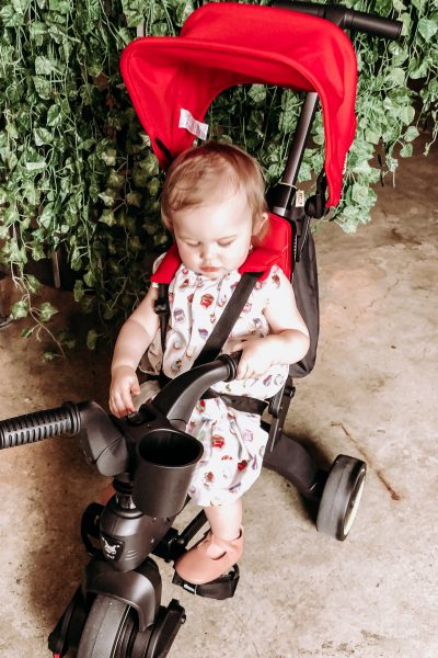 Liki Trike by Doona by popular California lifestyle and beauty blog, Haute Beauty Guide: Image of a baby girl sitting in a red Doona Liki Trike.