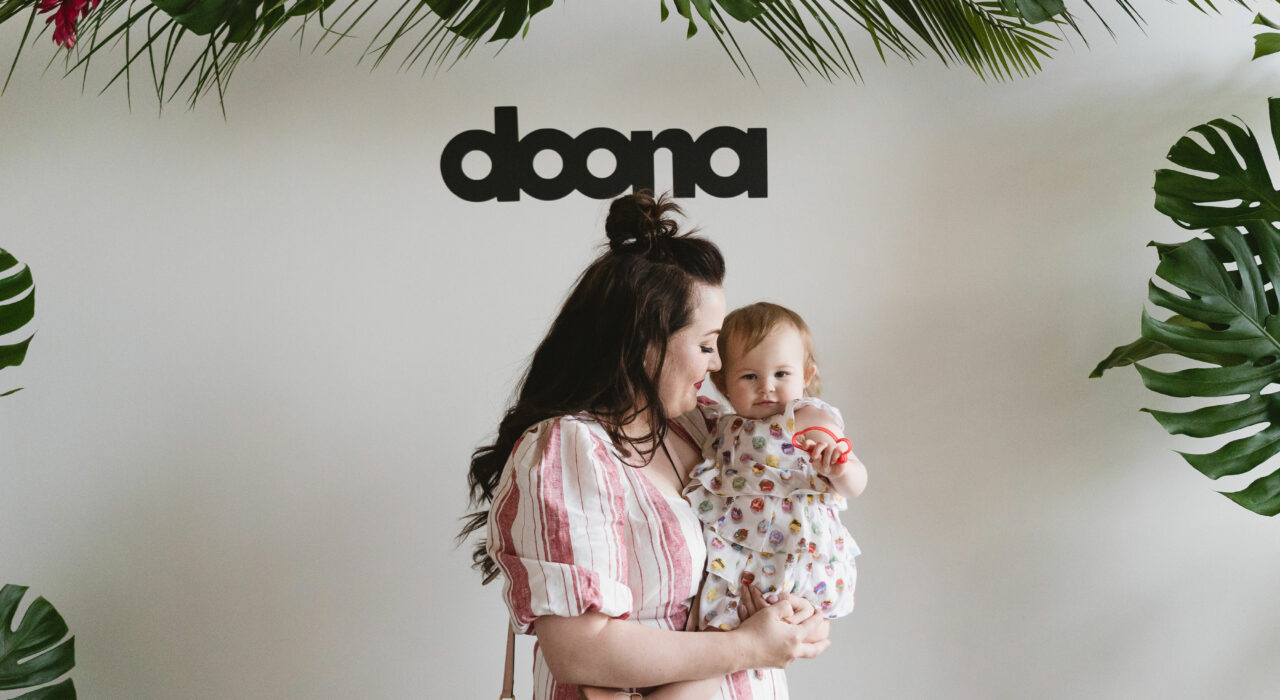 Liki Trike by Doona by popular California lifestyle and beauty blog, Haute Beauty Guide: Image of a mom and her baby girl posing for a picture at a Doona photo backdrop made from palm leaves and tropical flowers.
