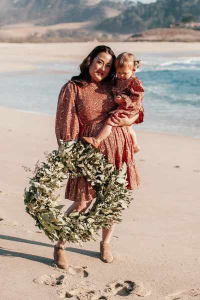 Mommy and Me Christmas Dresses by popular California life and style blog, Haute Beauty Guide: image of a mom holding a The Bougs Co. wreath and her daughter at the beach and wearing a Doen LEDA DRESS, Doen LITTLE ISLA DRESS, Vince Camuto booties, Sweet n Swag baby moccasins, Charlotte Tilbury lipstick and eyeliner, and Good Jane Fabulash Lashes.