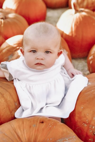 Bouchard Farms in Salinas, cA | The 3 Best Pumpkin Patches in Monterey County by popular California blog, Haute Beauty Guide: image of a baby sitting with some pumpkins.