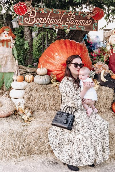 Bouchard Farms in Salinas, cA | The 3 Best Pumpkin Patches in Monterey County by popular California blog, Haute Beauty Guide: image of a mom holding her baby at a pumpkin patch.