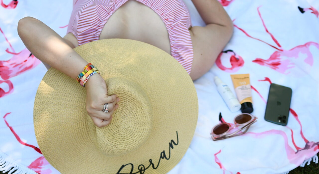 Swimsuits for Big Busts by popular Monterey fashion blog, Haute Beauty Guide: image of a woman laying by the pool and wearing a Aava OCEANE RETRO ONE-PIECE and straw sunhat.