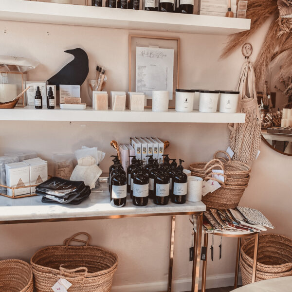 Haute Beauty Guide Studio by popular Monterey life and style blog, Haute Beauty Guide: image of various beauty and wellness products, woven baskets, candles, and books on white floating shelves.