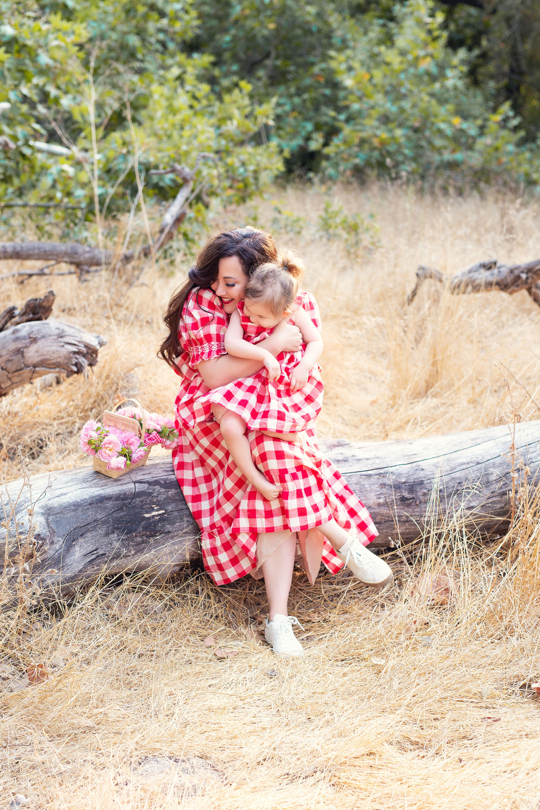 Holiday Card Ideas by popular Monterey lifestyle blog, Haute Beauty Guide: image of a mom and daughter wearing matching red and white buffalo plaid dresses and sitting outside on a log in a field of grass.