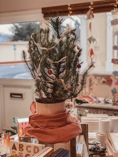 Holiday Items by popular Monterey life and style blog, Haute Beauty Guide: image of a Furoshiki wrap wrapped around a mini faux christmas tree base.
