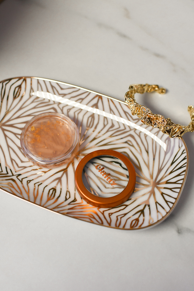Curateur Box Winter 2020 by popular Montery life and style blog, Haute Beauty Guide: image of a white and gold trinket dish, gold bracelt, and elaluz lip therapy.