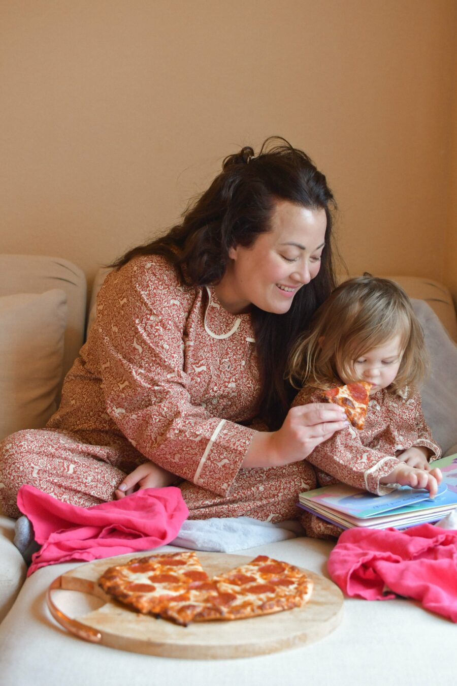 New Year's Resolutions by popular Monterey lifestyle blog, Haute Beauty Guide: image of a mom and her young daughter wearing matching pajamas and sitting in bed eating pizza.