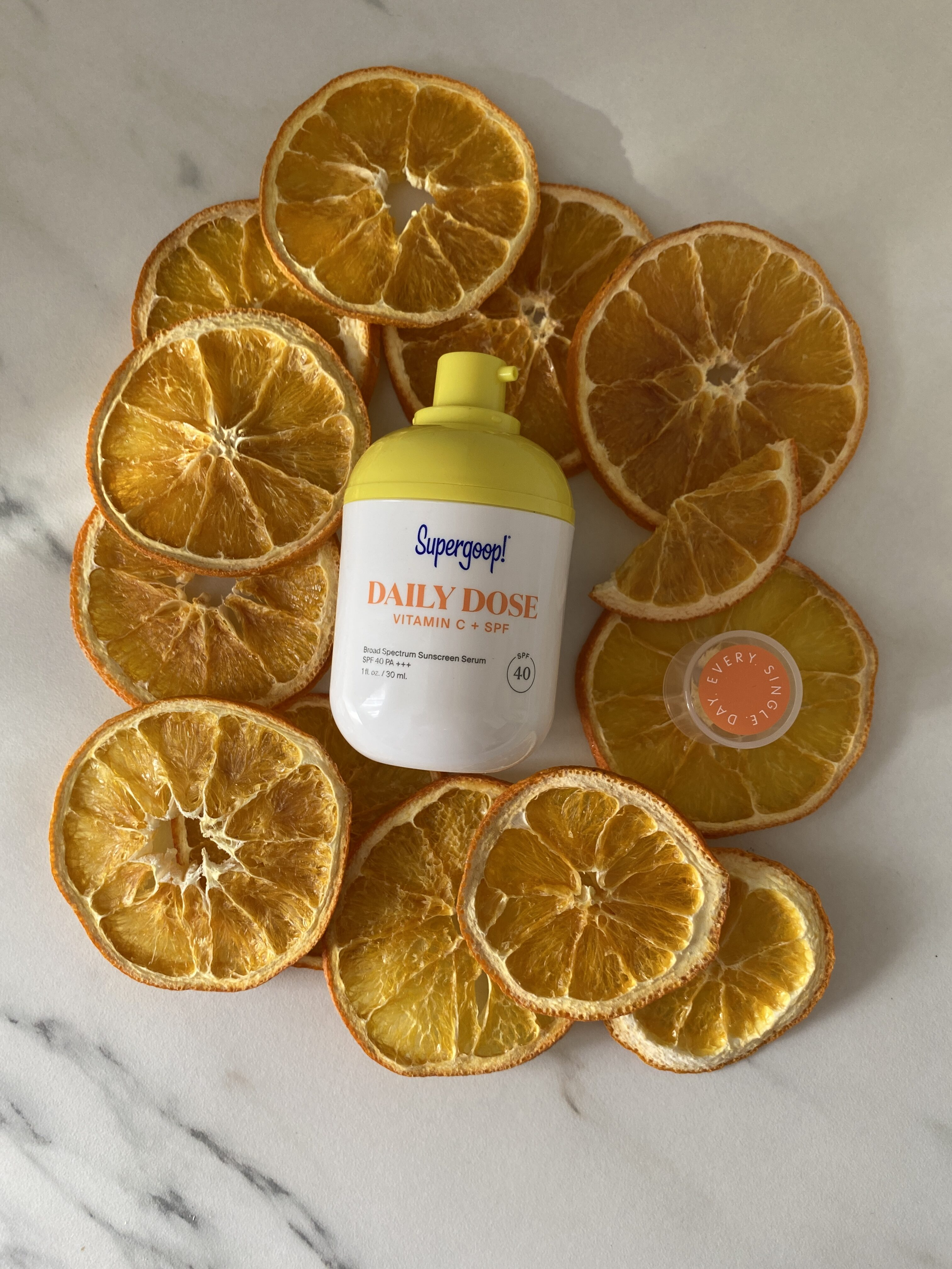 Supergoop Daily Dose Vitamin C + SPF 40 laying on top of dried oranges.