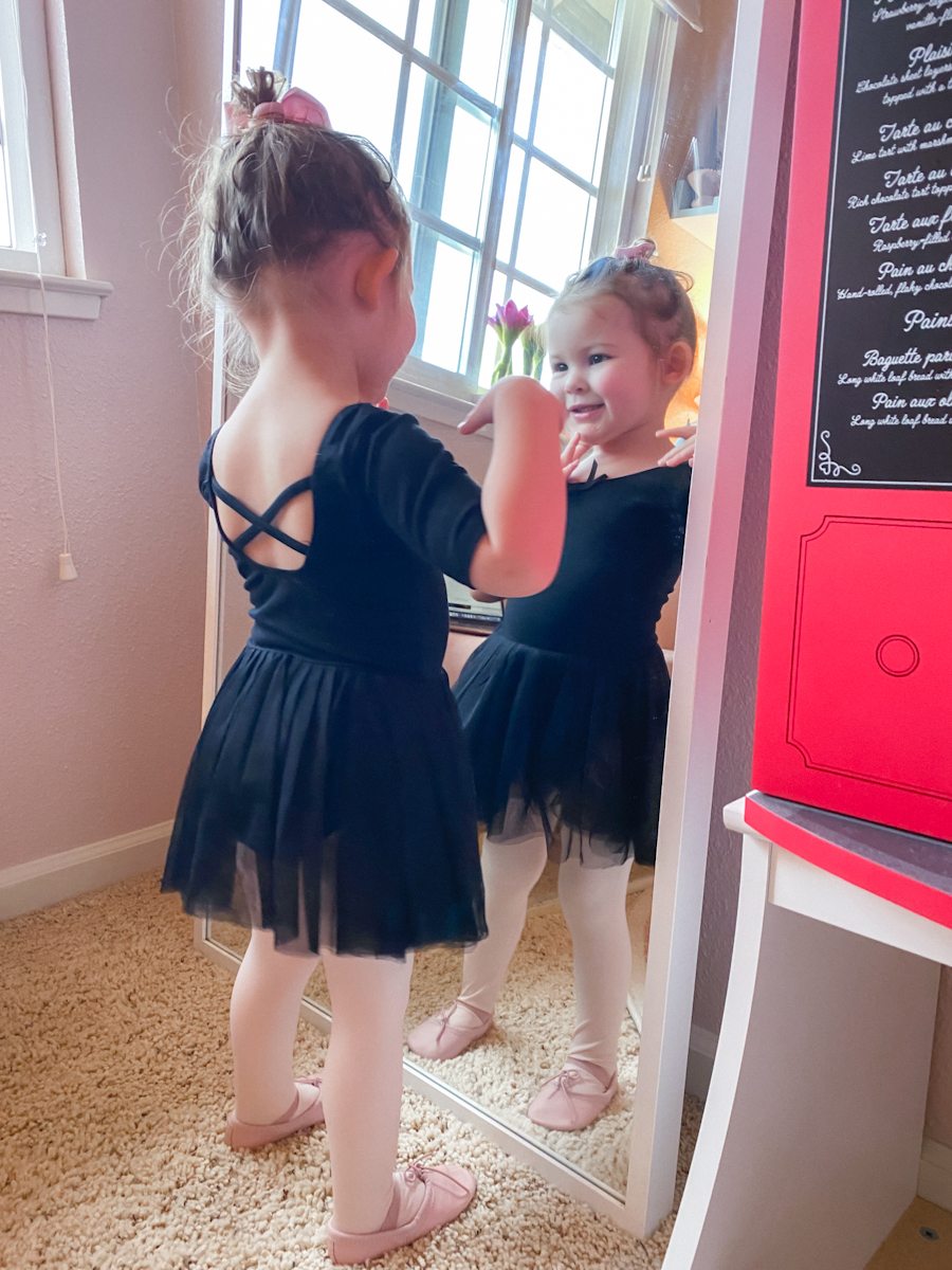 Hello Sawyer by popular Monterey motherhood blog, Haute Beauty Guide: image of a little girl wearing a black tutu, black leotard, pink tights, and pink ballet slippers while looking at herself in a full body mirror.