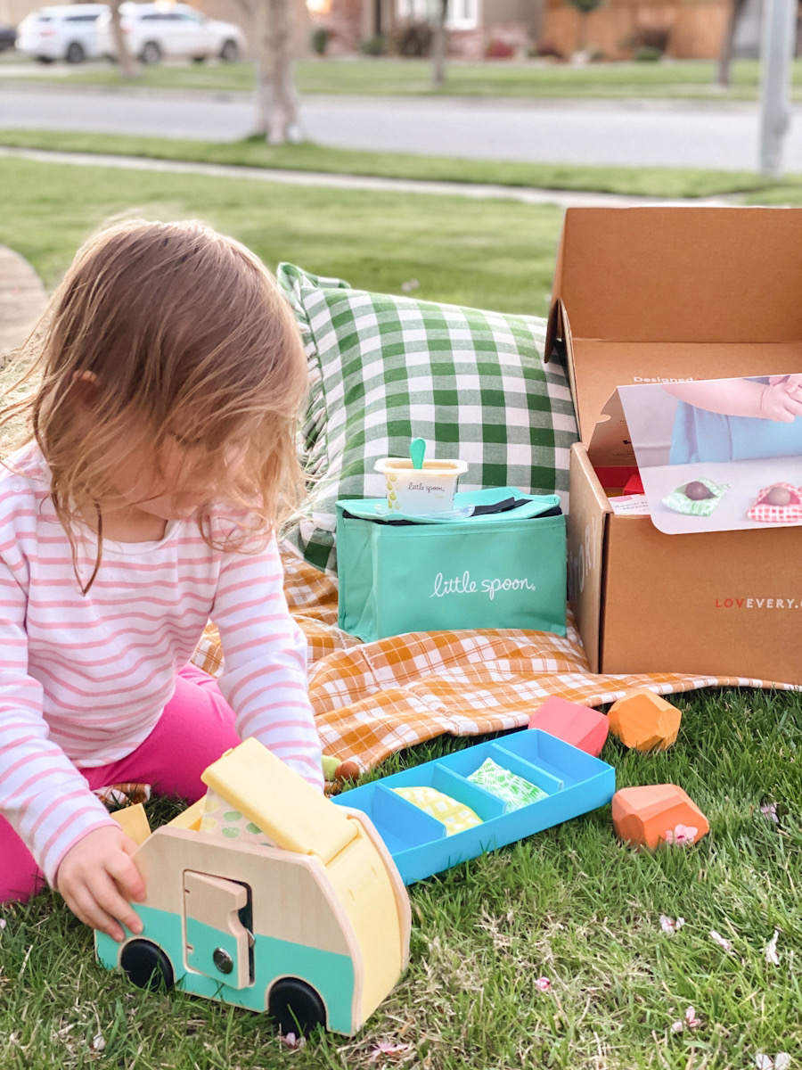 Toddler Speech Therapy by popular Monterey motherhood blog, Haute Beauty Guide: image of a little girl sitting outside next to some Little Spoon food items and playing with a wooden camper toy.