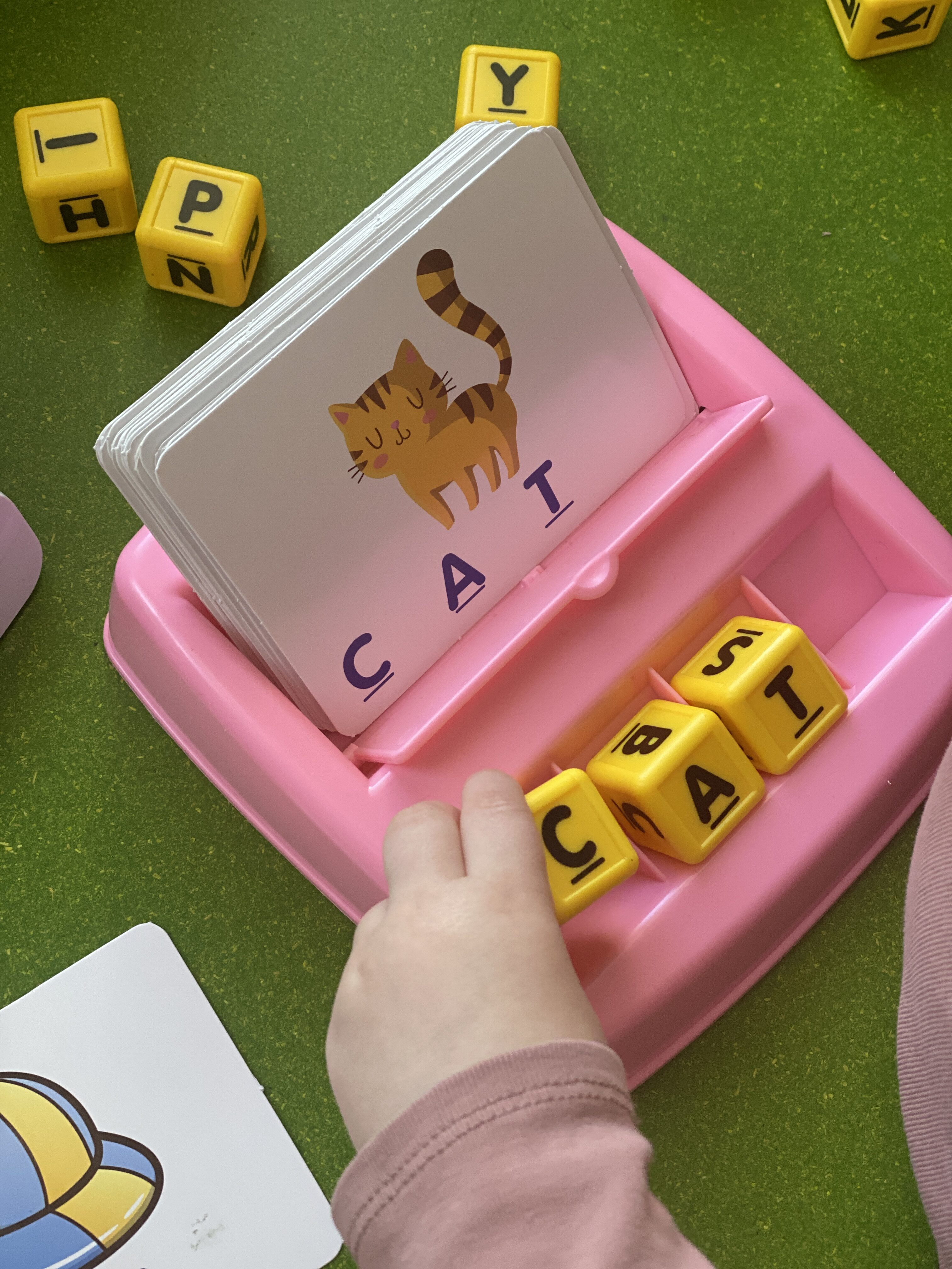 Toddler Speech Therapy by popular Monterey motherhood blog, Haute Beauty Guide: image of a little girl using a spelling toy and spelling out the word cat.