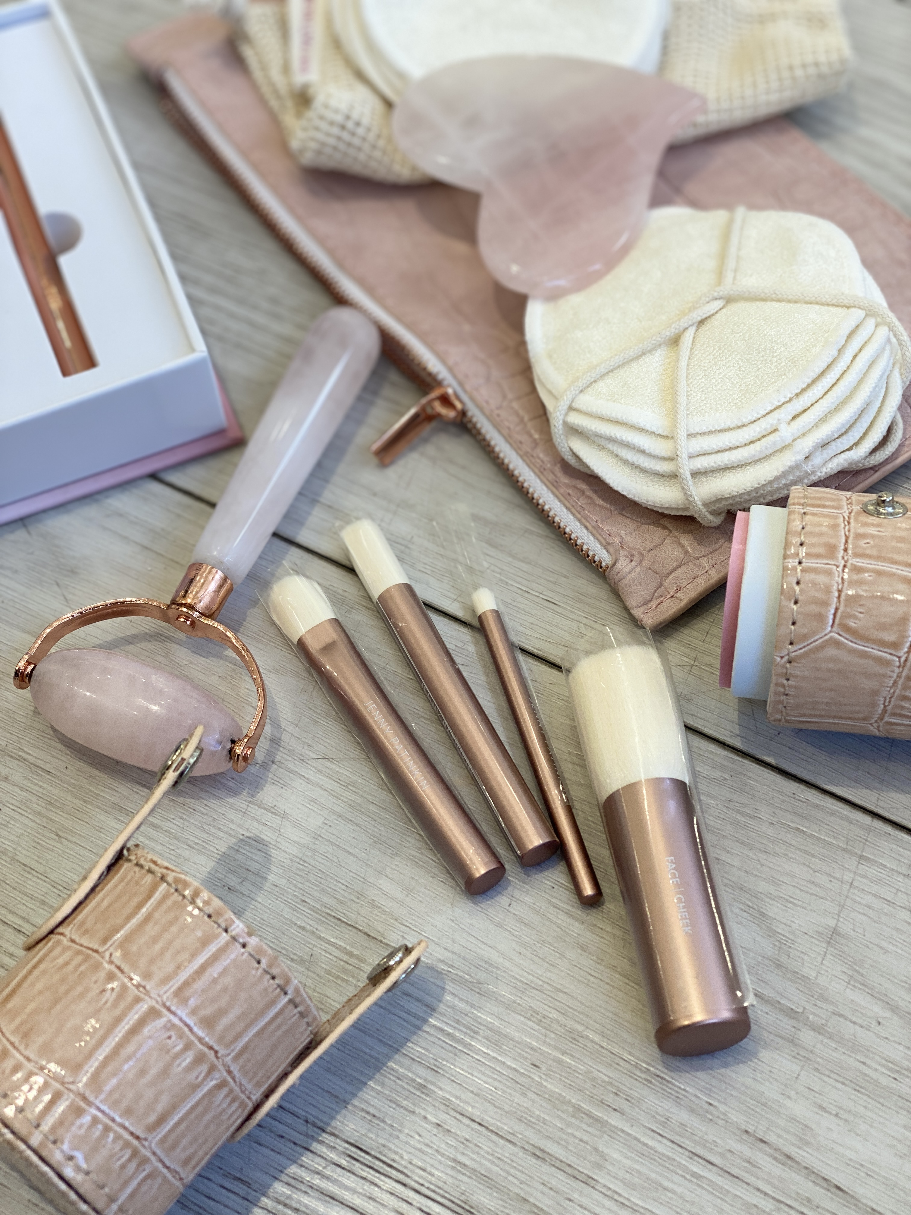 Cos Bar Sale by popular Monterey beauty blog, Haute Beauty Guide: image of a rose quarts face roller, make up brushes, and round cloth pads.
