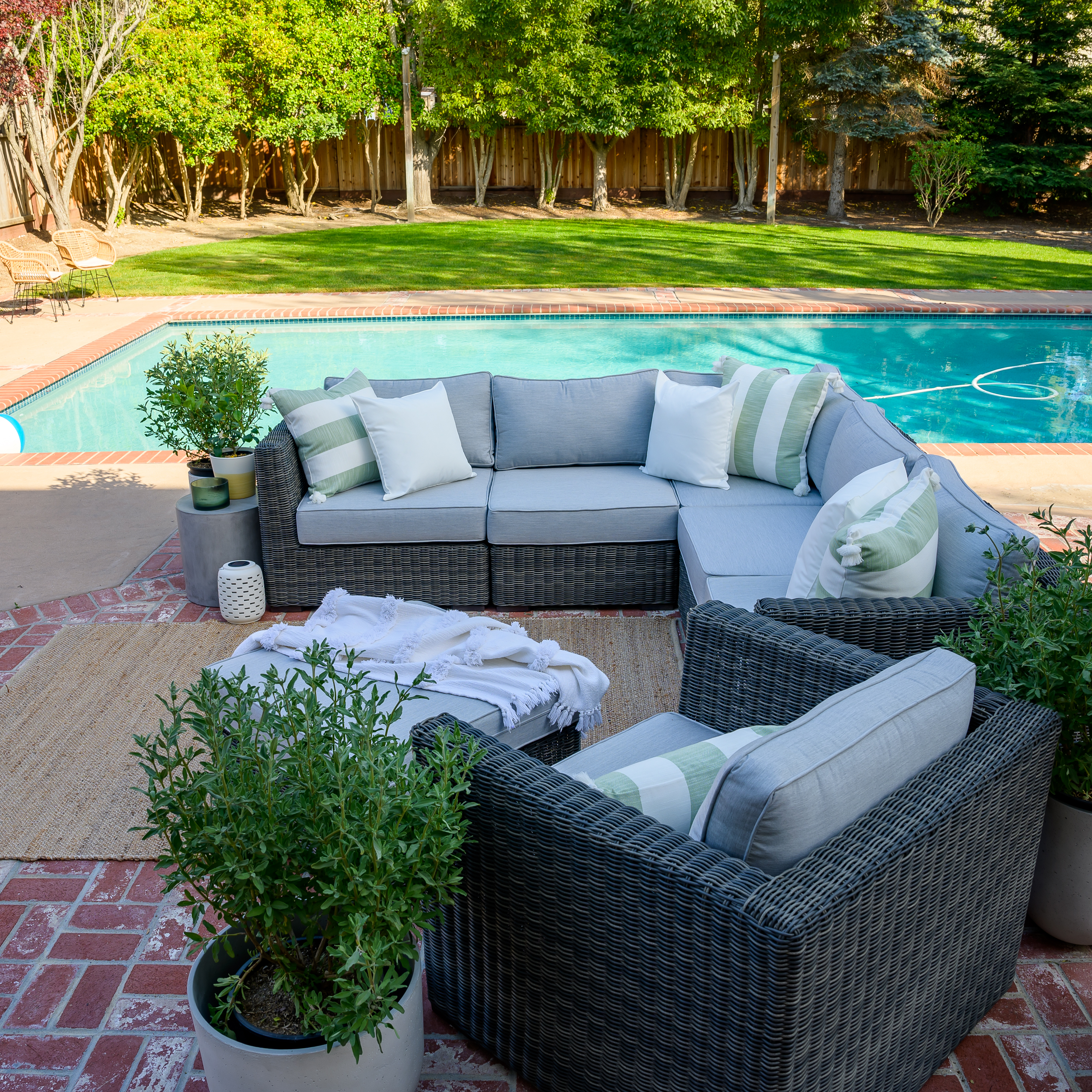 Outdoor Living Room by popular Monterey life and style blog, Haute Beauty Guide: after image of a backyard with a uncovered swimming pool, grass, and patio decorated with a jute area rug, grey wicker Ajna living sectional couch with grey cushions and white and green and white stripe throw pillows and a grey wicker Ajna living chair with grey cushions and a green and white stripe throw pillow.