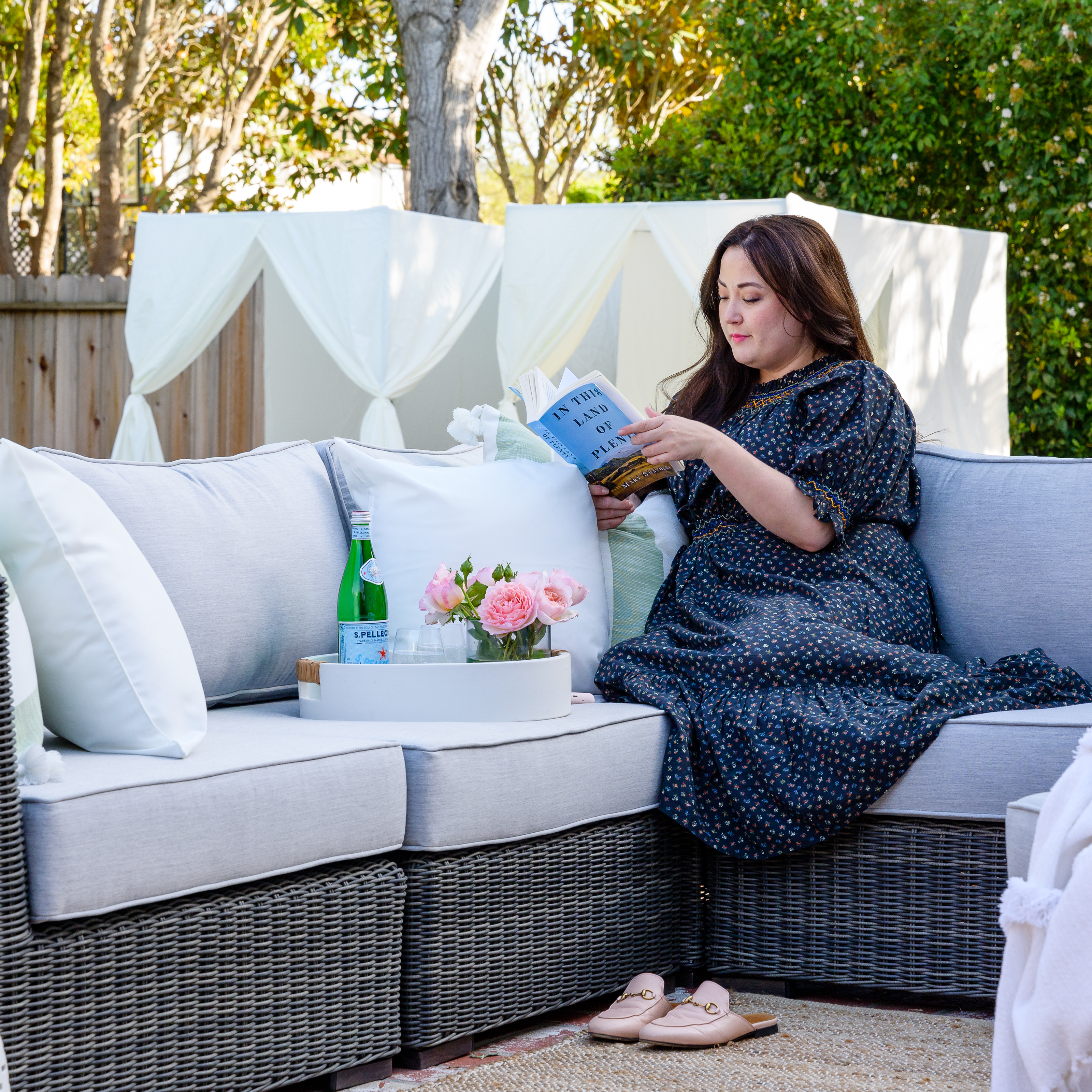 Outdoor Living Room by popular Monterey life and style blog, Haute Beauty Guide: image of a woman wearing a navy blue floral print maxi dress and sitting on a wicker outdoor Ajna Living sectional couch with grey cushions.