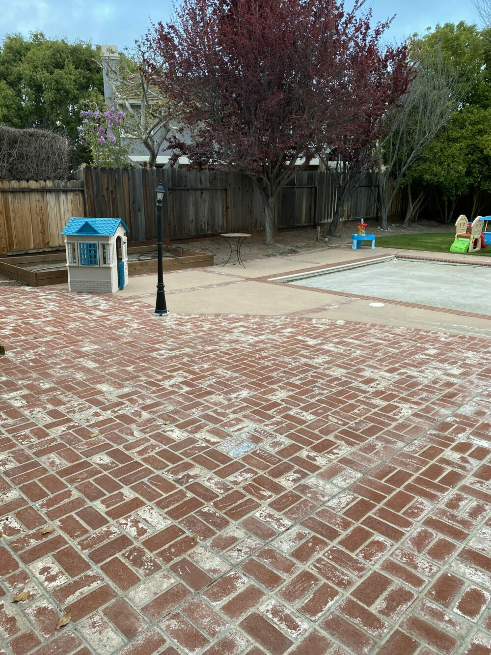 Outdoor Living Room by popular Monterey life and style blog, Haute Beauty Guide: before image of a brick patio with a black lamp post, covered swimming pool, and kids' playhouse.