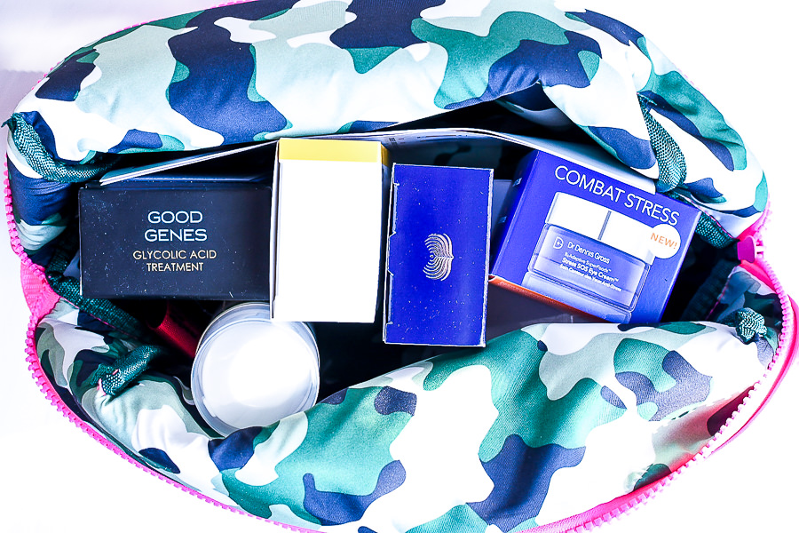 Caroline Hirons by popular Monterey beauty blog, Haute Beauty Guide: image of a pink makeup bag with blue, green and white camo lining that's filled with Good Genes Glycolic Acid Treatment, Dr. Dennis Gross Skincare, and other skincare products.