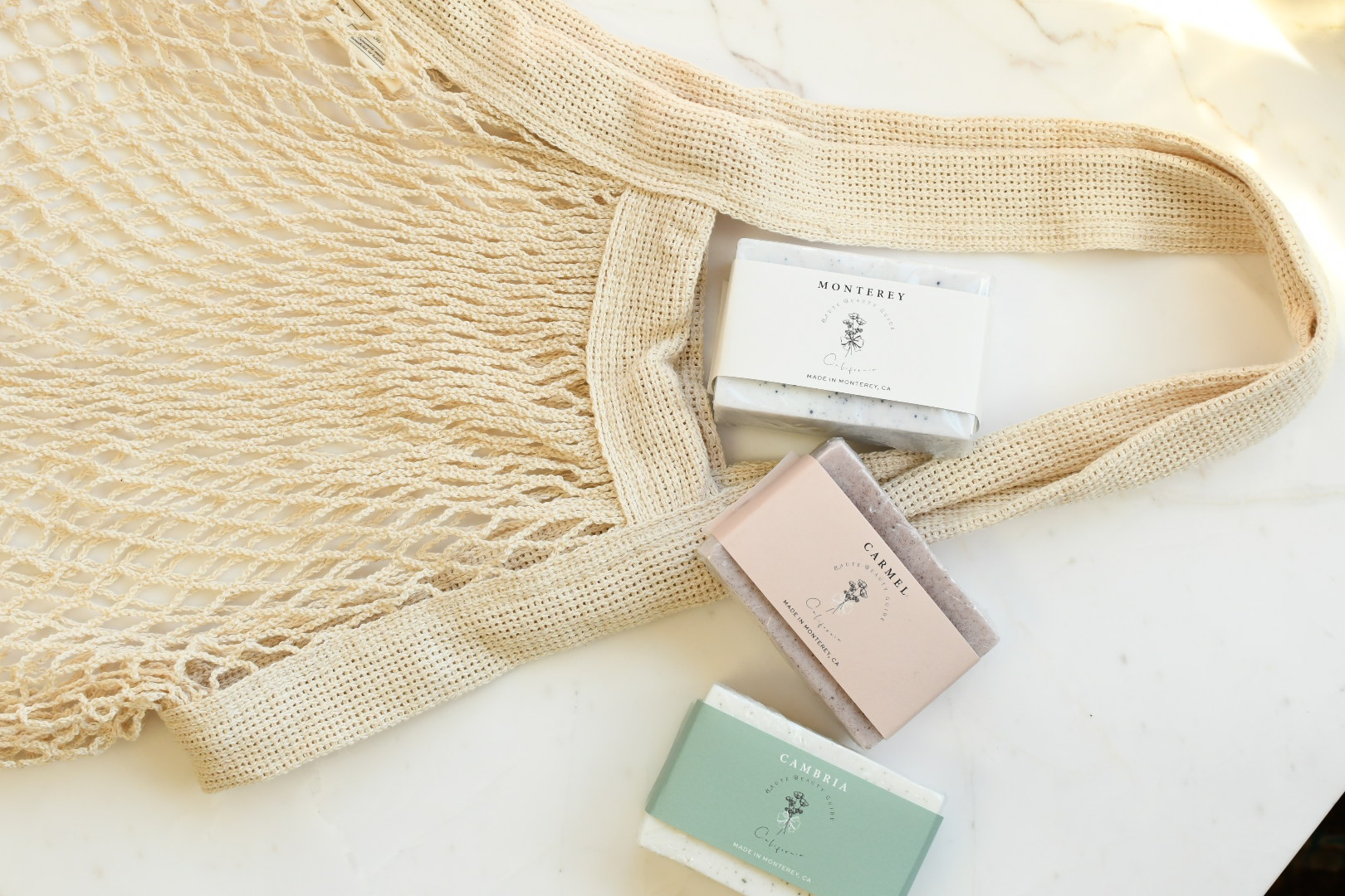 California Products by popular Monterey life and style blog, Haute Beauty Guide: image of California soaps next to a mesh shopping bag.