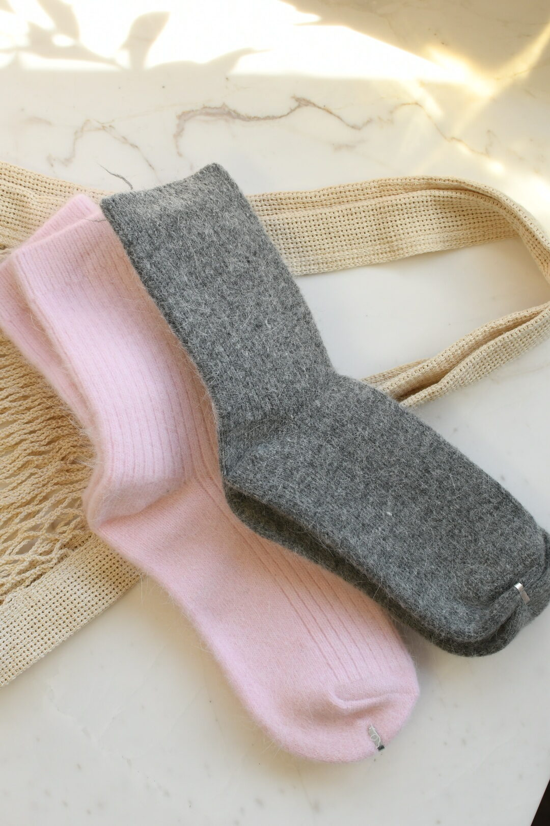 California Products by popular Monterey life and style blog, Haute Beauty Guide: image of cashmere socks next to a mesh shopping bag.