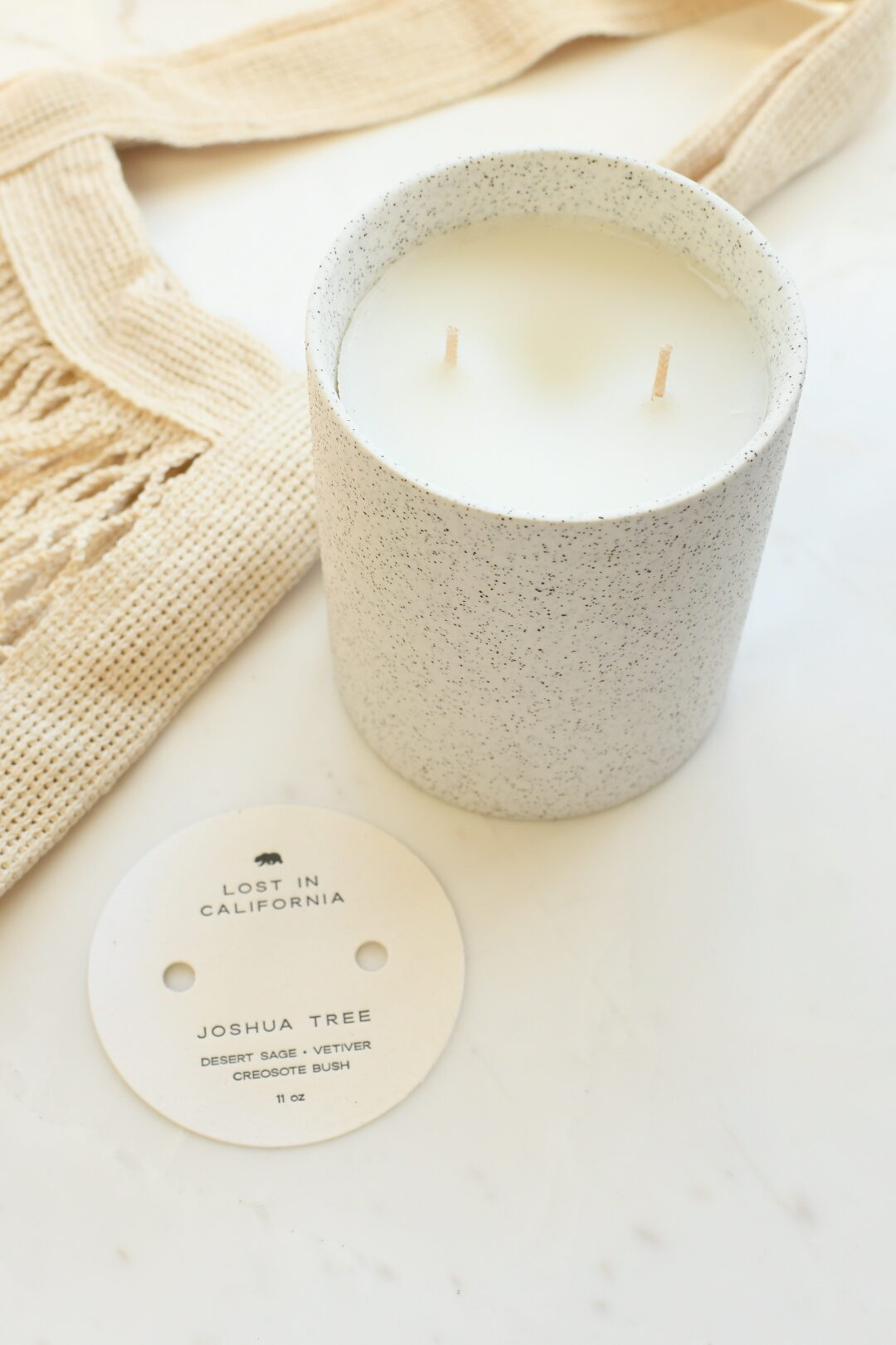 California Products by popular Monterey life and style blog, Haute Beauty Guide: image of a California inspired candle next to a mesh shopping bag.
