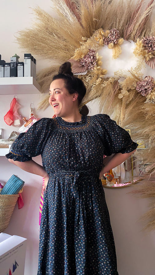 Haute Beauty Guide Shop by popular Monterey life and style blog, Haute Beauty Guide: image of a woman wearing a smocked neck blue floral print puff sleeve tie waist maxi dress while standing in front of round mirror that's next to a vase filled with pampas grass.
