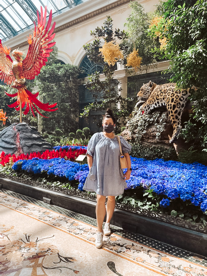 Las Vegas Trip by popular Monterey travel blog, Haute Beauty Blog: image of a woman wearing a grey and white gingham dress and standing in front of a floral display at the Bellagio hotel.