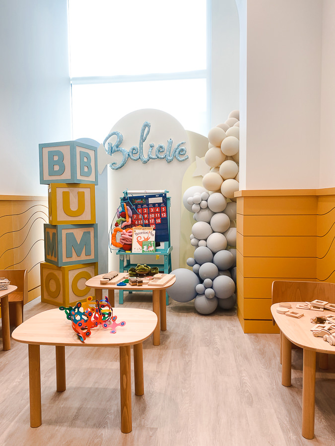BumoWork by popular Monterey motherhood blog, Haute Beauty Guide: image of a room with a grey ombre balloon garland, pocket chart holder, wooden tables with educational toys, and a life-size stacked letter block structure.