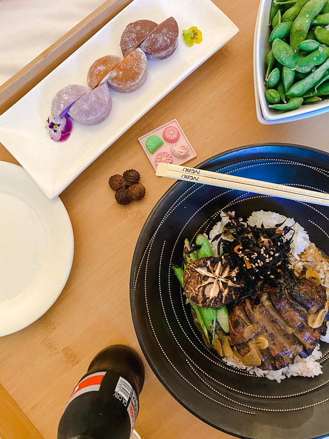 Palo Alto trip by popular Monterey travel blog, Haute Beauty Guide: image of a Japanese food on a black plate next to a white bowl filled with edamame.