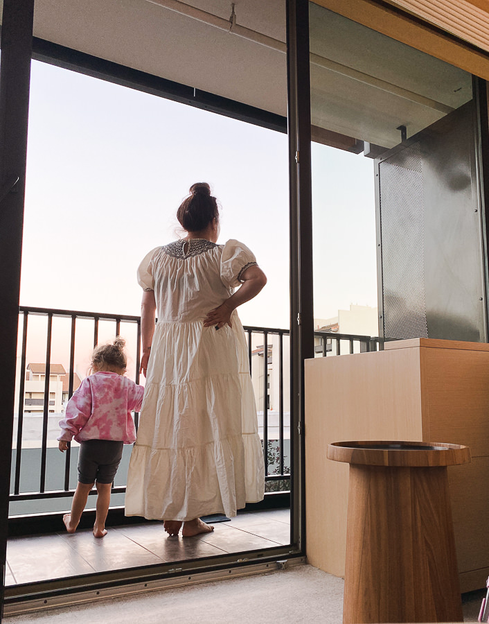 Palo Alto Trip by popular Monterey travel blog, Haute Beauty Guid: image of a mom and her young daughter standing together on a hotel balcony.