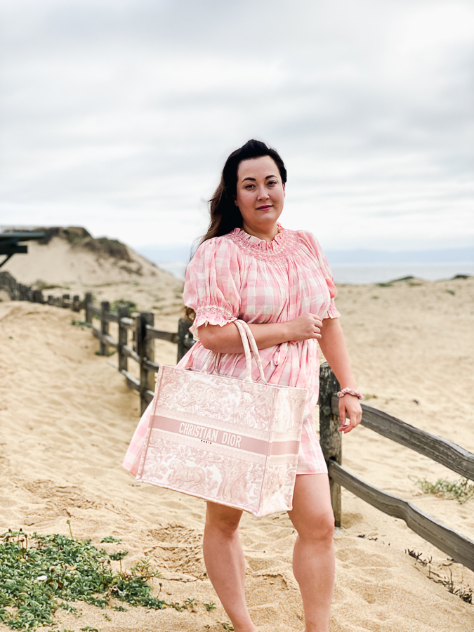 Designer Handbags by popular Monterey fashion blog, Haute Beauty Guide: image of a standing in the sand at the beach and wearing a pink and white gingham dress while holding a pink Christian Dior tote bag.